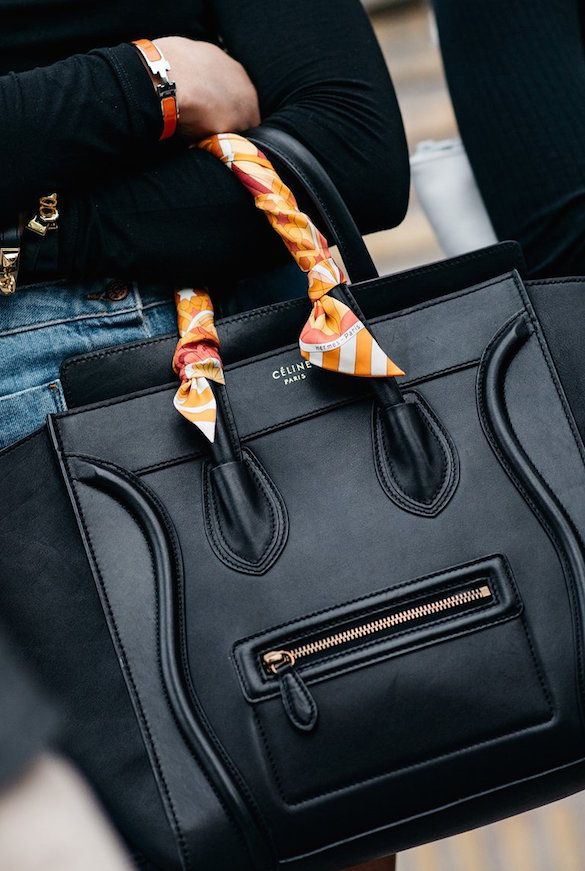 Black Céline luggage tote with a Pucci scarf wrapped around one handle + an Hermès bracelet