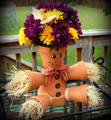 "I made this scarecrow for my MIL birthday! I think it turned out pretty cute.. it is well OVER 2' tall.. I used 8"" for the bottom, 6"" for the top and 4"" pots for the side, designed the face, added raffia, flowers and used E6000 to hold it all together:) The grooved clay pots give this character all it's own !  See other clay pot creations at http://www.pinterest.com/paulapie40/faux-bubble-gum-machine-candy-jars/"