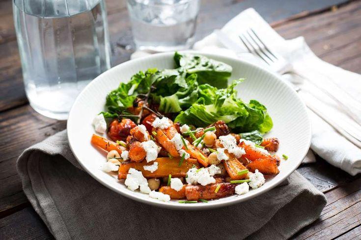 Recept voor geroosterde zoete worteltjes voor 4 personen. Met zout, olijfolie, peper, wortelmix, trostomaat, mini romanasla, komkommer, tijm, kikkererwten, geitenkaas, honing, bieslook en balsamico azijn
