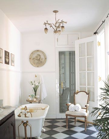 Double French doors in a French-style New Orleans cottage's master bath designed by Karyl Pierce Paxton. The sink base is an 18th-century French buffet with Kohler fixtures. Love using furniture as a vanity- House Beautiful