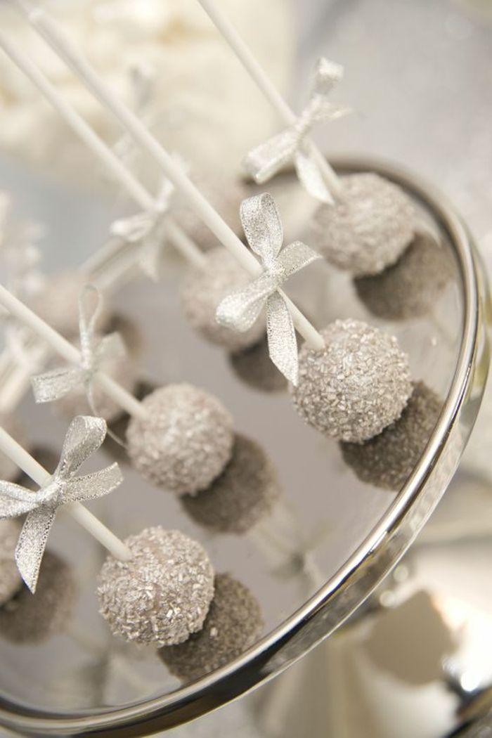 silberner servierteller mit kuchen am stiel dekoriert mit kokos