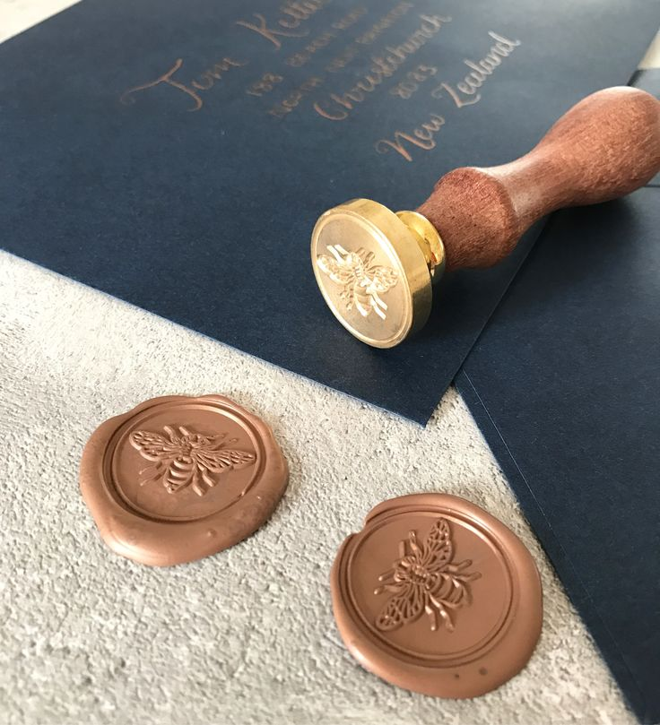 This bespoke wedding invitation order was finished with calligraphy addresses on luxury navy envelopes and a bronze bee wax seal