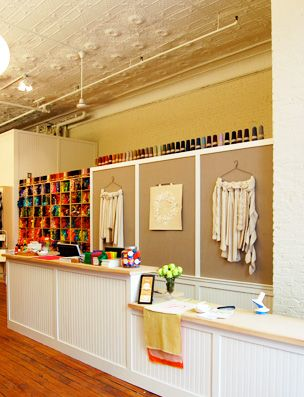Purl Soho yarn shop in New York. Love the graphic, framed art look of wall behind register. Watch for a version at Yarntopia.