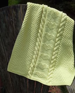 This cuddly baby blanket includes cables and textured stitches to create a column of hearts in the center.