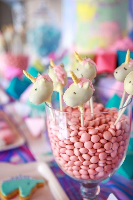 Os bolos no palito ganharam o formato de cabeças de unicónio e foram arrumados no vaso transparente, recheado de confeitos cor de rosa. Parece que eles estão observando a mesa...