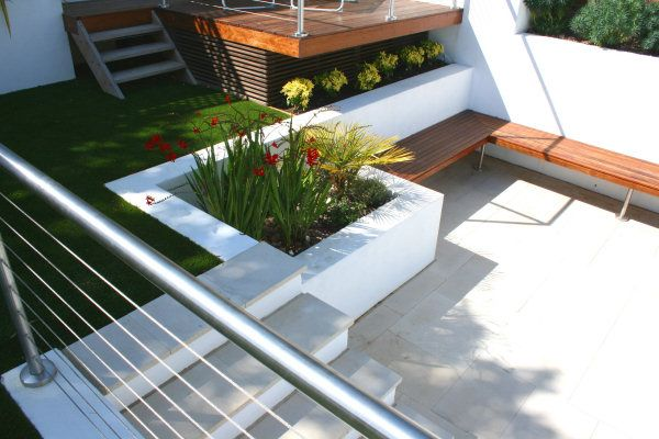 Tiered garden combining smooth natural stone paving, white rendered walls, hardwood decking and stainless steel railings with Mediterranean style planting and  artificial grass lawn for ease of maintenance