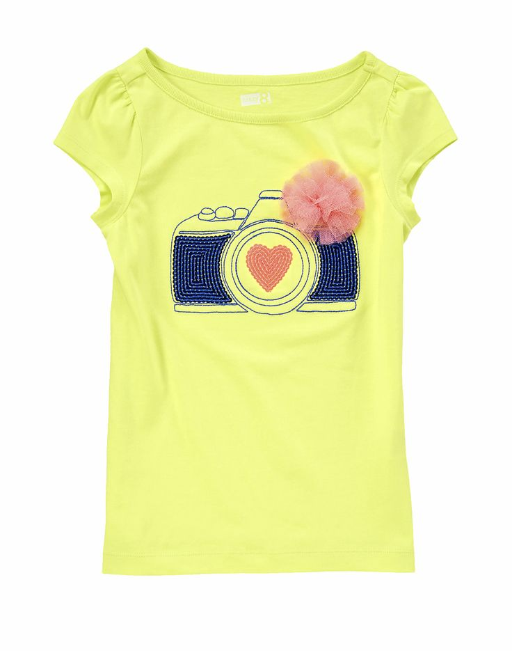 Brights, camera, action! Shimmery camera tee topped with a pretty pouf.WARNING: CHOKING HAZARD - Small parts. Not for children under 3 yrs. - picked this up for Campbell tonight... love it!