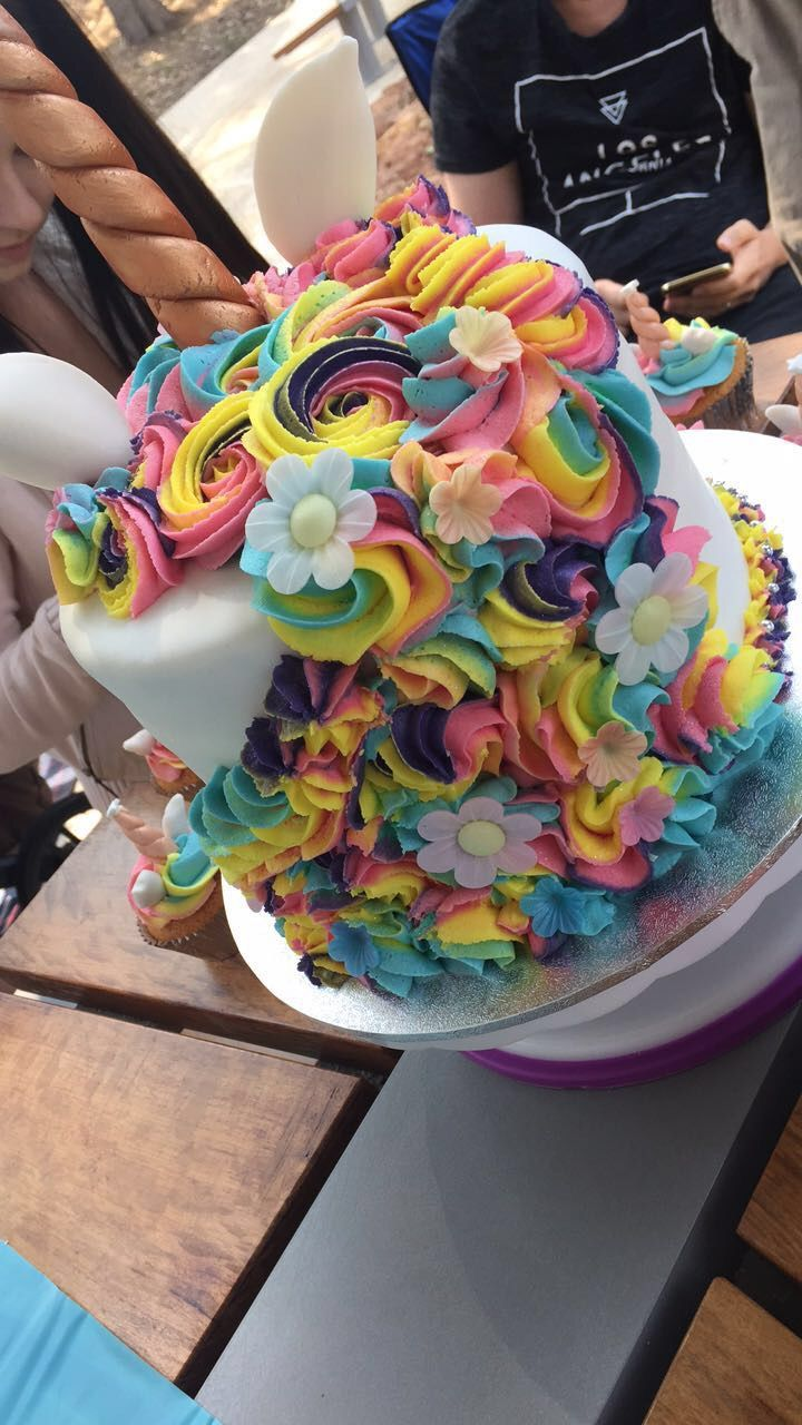 Unicorn cake with mini unicorn cupcakes with rainbow butter cream and glitter