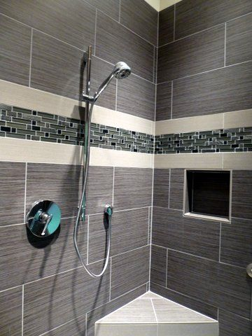 Custom walk in shower using a large profile tile with a nice linear band for an accents.