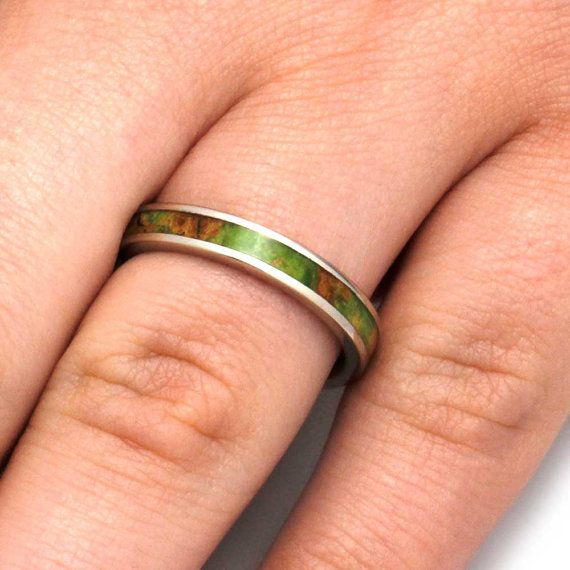 A band of gleaming white gold provides a home for this remarkable wood ring. The peridot box elder burl makes for a sensational womens wedding band with true character. The stand out wood grain of the peridot burl is an eye-catching delight.  This ring comes with FREE ring armor waterproofing (a $75 value).  RING PRICED FOR THESE SPECIFICATIONS Ring Size: 7.25 Ring Width: 3 mm Ring Sleeve: 10k White Gold Ring Profile: Flat Ring Finish: Polished  0.5 mm 10k White Gold 2 mm Peridot Box Elder…