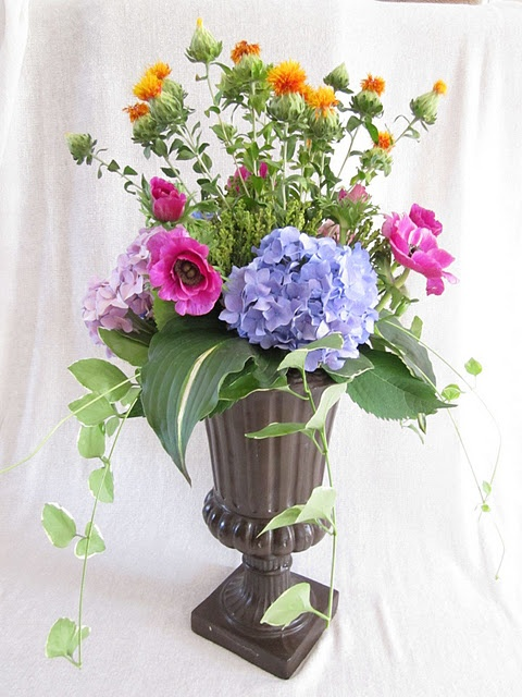 Garden arrangement of hydrangea, hot pink anenomes, orange Safflower, hosta and vinca vines.   design by Stems Flower Market. Allison, see the safflower? It's not always that orangey, usually more yellow in it. I thought you would like the shape and texture.