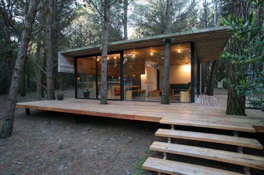 Em meio a natureza o projeto criou um deck com coloração clara que deixa o espaço para as árvores se desenvolveram. A casa com paredes de vidro substitui o uso de laje pelo forro de madeira.