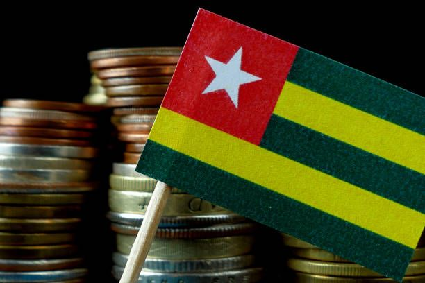 togo flag waving with stack of money coins macro