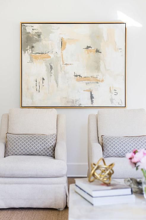 Alyssa Rosenheck- Laurel Powell - Beautiful living room a gold and gray abstract canvas art piece which stands over a pair of light gray curved-arm chairs accented with gray lumbar pillows.