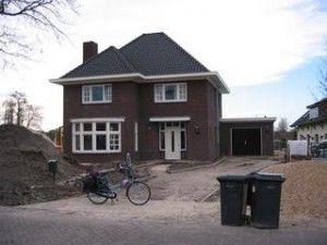 Nieuwbouw jaren 30 woning. Uitstekend deel met eigen dak. Voordeur met aan weerszijden een raam.