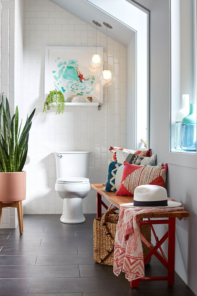 Timeless bathroom design (charcoal grey tile floor, subway tile walls) with quirky, colorful accessories