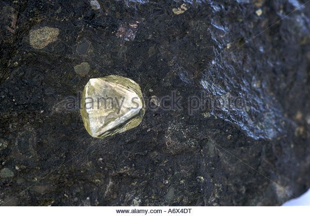 A yellow diamond embedded in a piece of kimberlite rock. - Stock Image