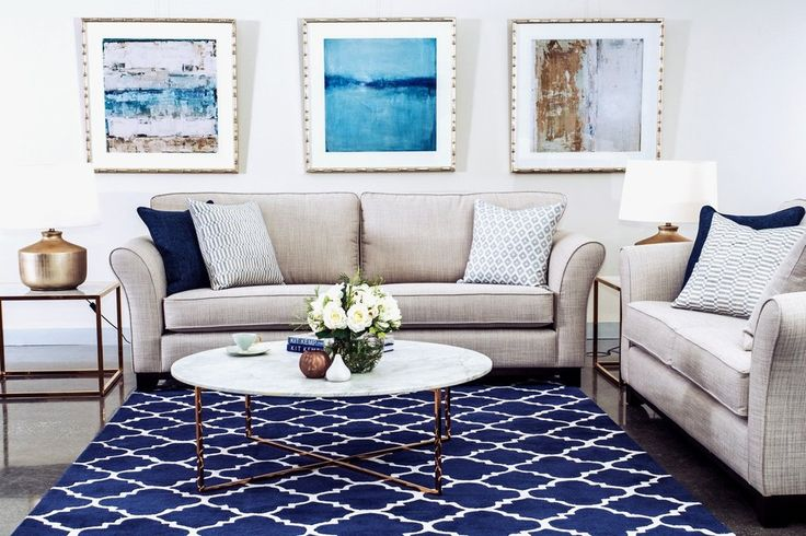 Chloe Sofa range styled in a neutral beige paired with marble and brass coffee table and navy blue accents in cushions and rug.
