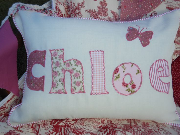 A cushion with the name Chloe ordered in pink paisley fabric with stripes and checks.