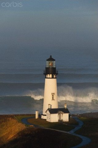 The historic Yaquina Head tower lighthouse on a headland overlooking the Pacific coastline.