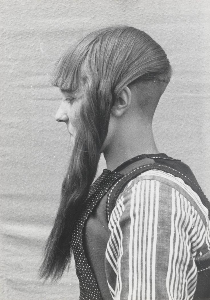 Meisje uit Marken met typische haardracht. Het haar wordt verdeeld in twee pijpenkrullen en een pony. In de nek wordt het haar opgeschoren. Deze haardracht wordt gedragen in combinatie met de 'grote kap'. 1943 #NoordHolland #Marken
