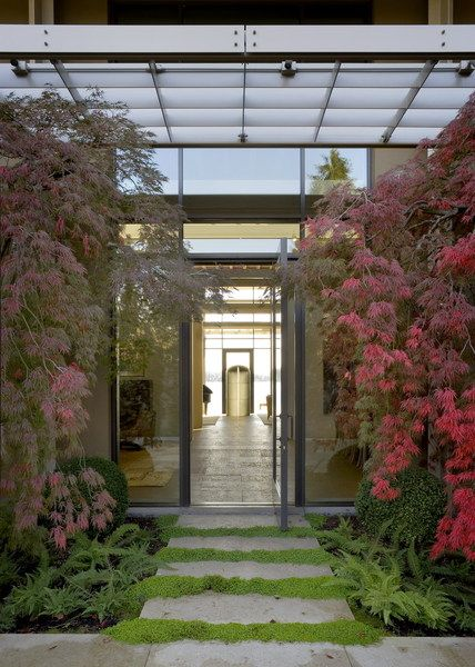 Entry to House of Light, steel house surrounded by lush garden; Jim Olson