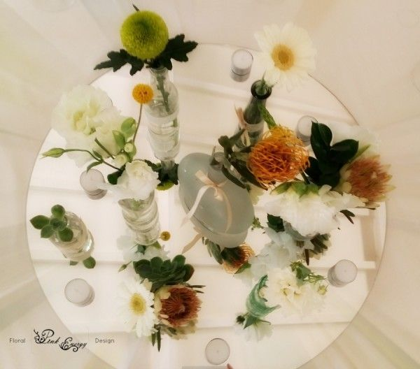 Indigenous themed wedding flowers in interesting small bottles and vases. Hertford Country Hotel, Johannesburg. Artistic photo taken from directly above the centerpiece. Floral Design & Decor  by www.pinkenergyfloraldesign.co.za