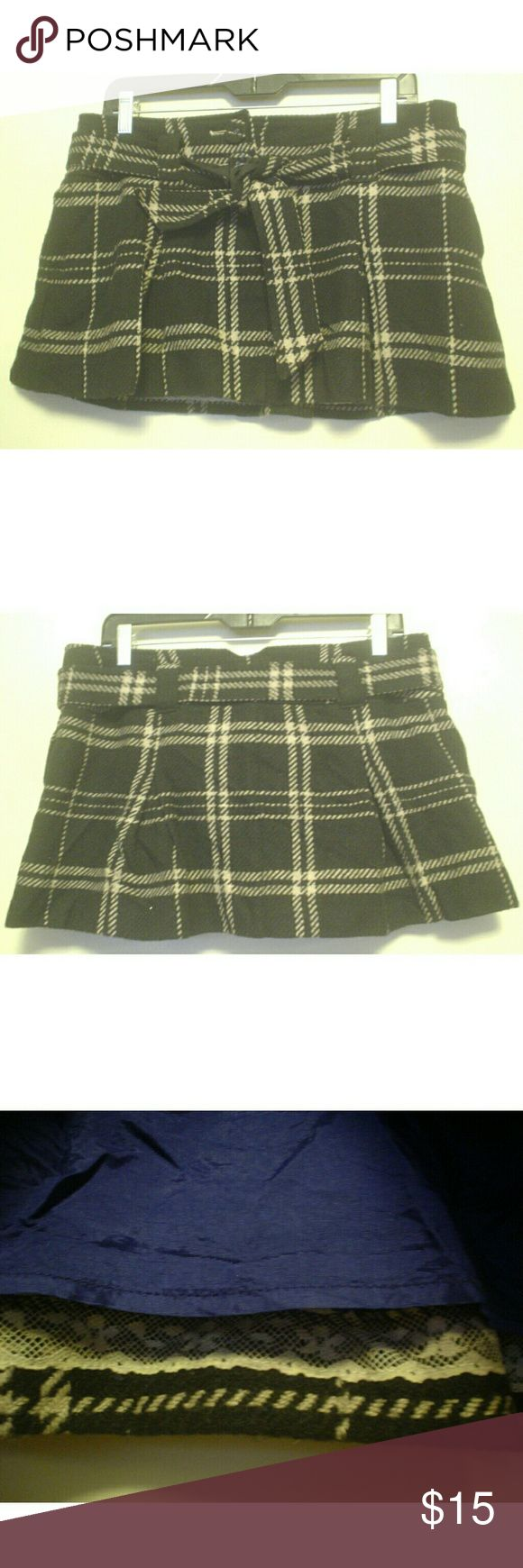 American Eagle Wool Plaid Schoolgirl Mini Skirt 10 American Eagle  Black and White Plaid Mini Skirt Schoolgirl Look Wide Self Tie Belt Purple Acetate Lining Two Button / Zip Front Close Side Seam Pockets Size 10  60% Wool / 40% Viscose Lining 100% Acetate   Measurements:  Waist: 18 Inches. Hips: 24 Inches. Length: 13 Inches.  I have inspected the skirt and found no rips, stains or flaws. American Eagle Outfitters Skirts Mini