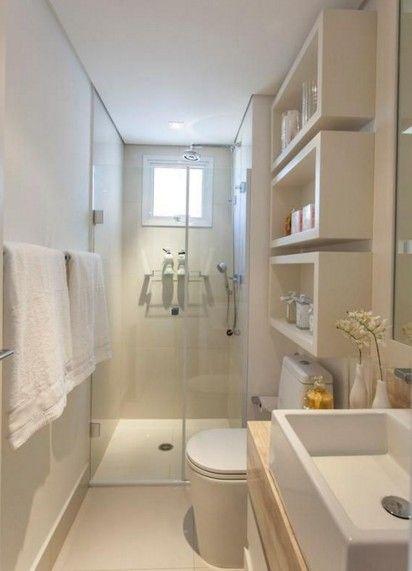 Cuarto de baño rectangular pequeño con ducha amplia al fondo y tonalidades blancas