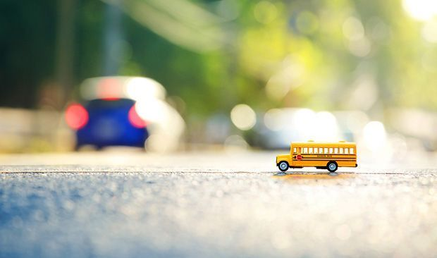 For this image, the photographer used a large aperture to help create the shallow depth of field. This is evident due to the brightness of the image.  The photographer also kept a closer distance to the subject, the toy school bus. This kept it in focus for the shallow depth of field.