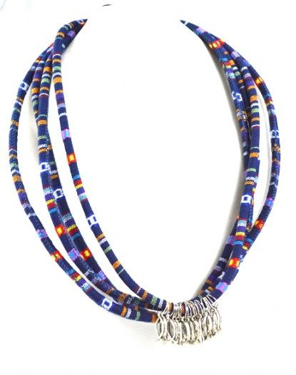 Sales price: 21,90 € incl. all tax Cocoon Short Necklace made up of blue fabric cord embellished with silver metallic fishes. Detail: the clasp. Total length approx. 68 cm. Gift box.