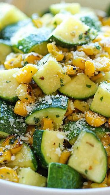 PARMESAN ZUCCHINI AND CORN = 2 T olive oil 2 cloves garlic 4 zucchinis, diced 1 cup corn kernels, frozen, canned or roasted 1/4 t dried basil 1/4 t dried oregano 1/4 t dried thyme Kosher salt and freshly ground black pepper Juice of 1 lime 2 T chopped fresh cilantro leaves 2 T grated Parmesan====