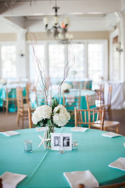 Aqua table cloths with beachy centerpieces including white hydrangea floral arrangements and starfish {Judy Nuñez Photography}