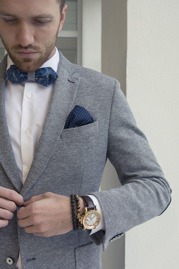 Modrý motýlek s paisley vzorem je oboustranný a může se tedy uvázat na 4 způsoby. Druhá strana má šedivou texturu a tak lze docílit super kombinace se šedým sakem. S motýlkem perfektně ladí kapesníček do saka. Pro doladění outfitu slouží náramky z lávových kamenů a hodinky se zlatými detaily.  #bowtie #pocketsquare #polkadot #bracelet #watch #menstyle #suit  Grey suit with blue bowtie and blue navy polka dot pocket square is perfect combination. Finish the look with nice watch and bracelets.