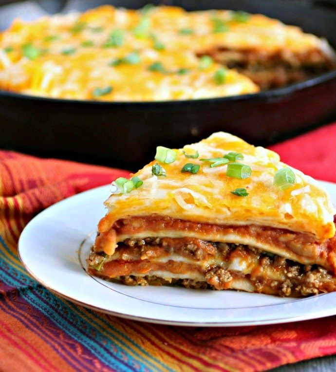 Mexican Tortilla Pie- cast iron skillet full of refried beans, enchilada sauce, and taco seasoned ground beef, separated by layers of tortillas, all topped off with cheese!