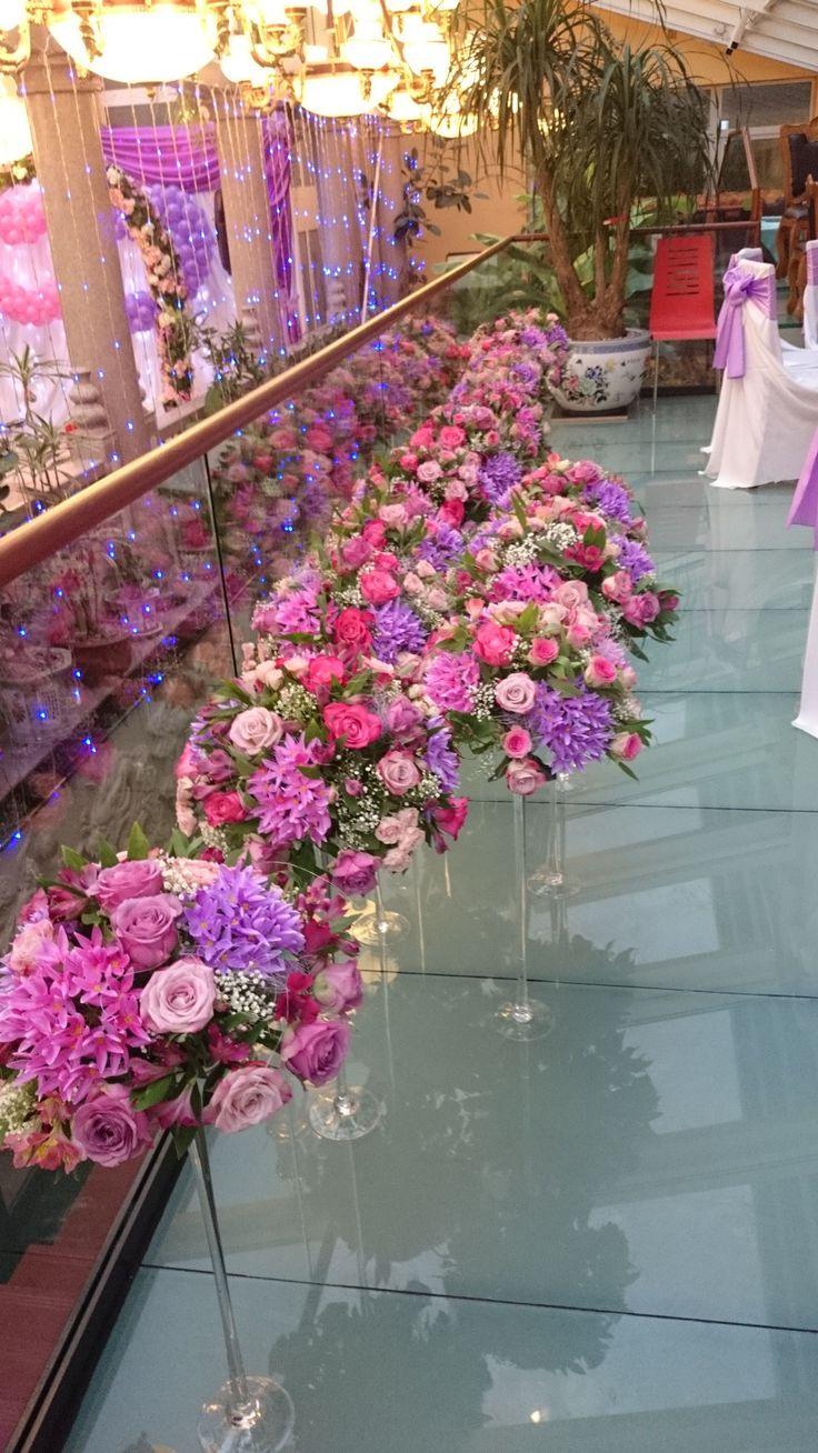 Pink és lila virágos esküvői asztaldíszek magas, vékony vázában.
