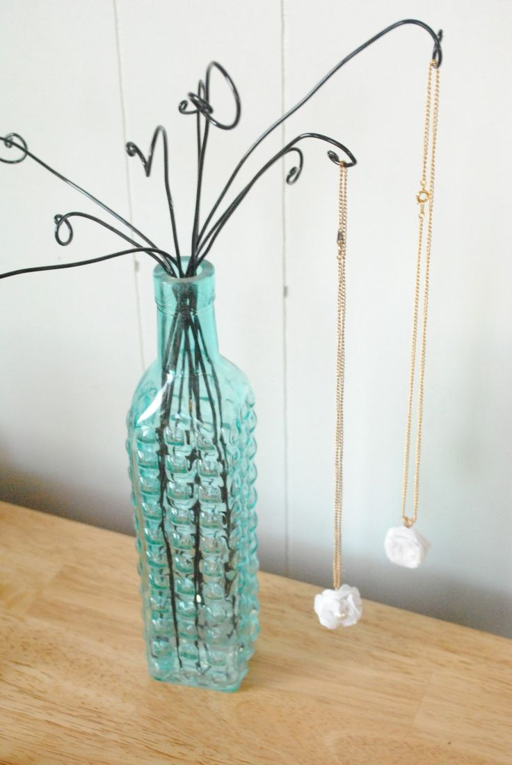 Wire hangers opened up and inserted in a pretty bottom for hanging necklaces.