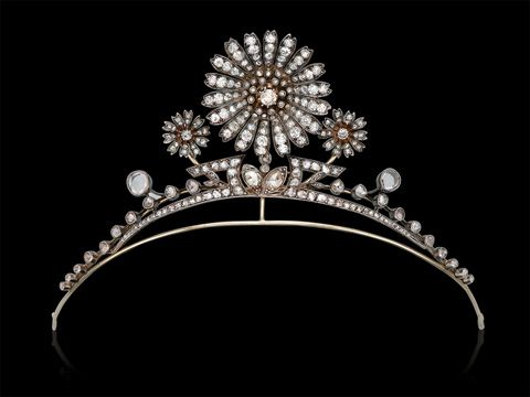 A Victorian Diamond Tiara c1890. Featuring a central flower blossom mounted en tremblant and accented by a pair of smaller florets, to the bandeau decorated with foliage and berries, entirely set with old mine and rose-cut diamonds. The principal blossom detachable to be worn as a pendant.