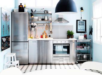 Cozinha em aço inoxidável com um frigorífico/congelador no lado esquerdo, armários no meio e um forno com placa e exaustor no lado direito Arrumação extra sobre rodas no canto, com prateleiras abertas em aço sobre a bancada