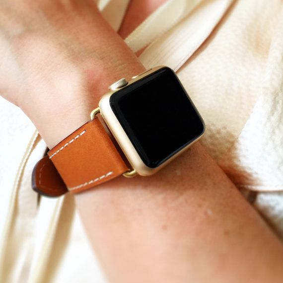 Brown hand-stitched Apple watch leather band with OPTION for silver, gold, rose gold, space gray or black hardware. This band has off-white stitching. This soft leather band is exquisitely elegant. Its artful simplicity is the perfect pairing to the Apple watch. It has high quality craftsmanship and is both a great tool and a bold statement. Only the band is for sale; it does not include the Apple watch.  Very easy to attach. No tools necessary. Limited supply.  ADAPTER SIZE   42m...