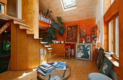 Z ateliéru vede dřevěné schodiště do malé otevřené ložnice.