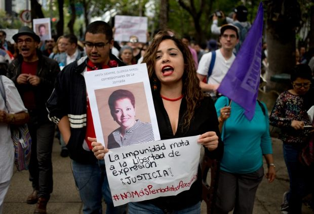 """w/too many dead journalists, Ciudad Juarez newspaper shuts down instead; """"During a March 25 protest in Mexico City, a woman holds a photo of slain Mexican journalist Miroslava Breach and a sign: 'The impunity kills freedom of speech, justice.'"""" ( Photo: Eduardo Verdugo/Associated Press)"""