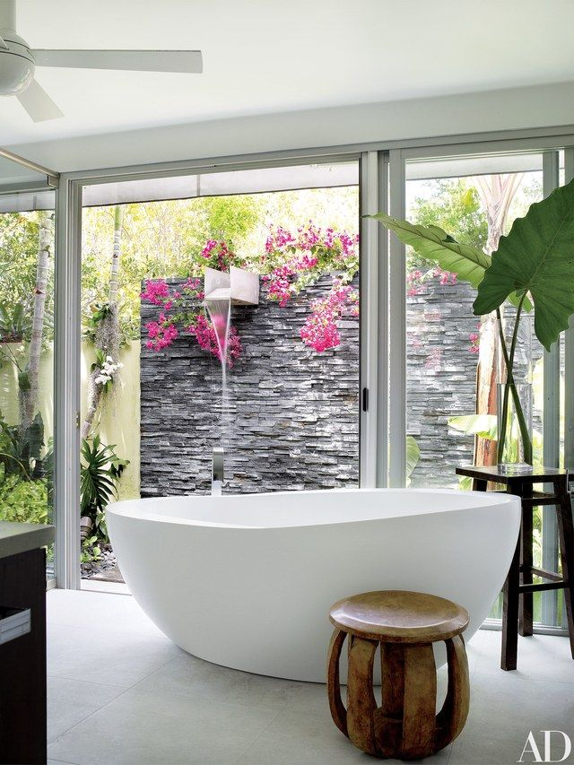 A Waterworks tub in the master bath faces a slate-walled waterfall shower, bringing the indoors and outdoors seamlessly together | archdigest.com