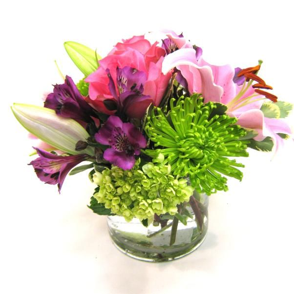 The contrasting pink and green flowers in this low cylinder vase will make any day a Happy Day!