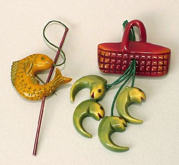 Two Bakelite Brooches The first with a fishing basket suspending four fish, the second depicting a fish caught on a fishing rod. Heights 3 3/4 inches.  Sold for $500  (2000)