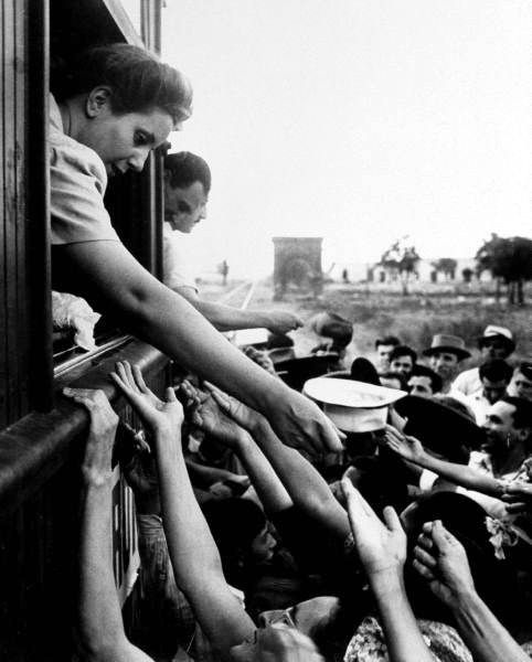 Eva Peron passing out campaign buttons from the window of a train as her husband Juan greets an enthusiastic crowd during his campaign trip. Photograph by Thomas D. McAvoy. Argentina, February 1946.