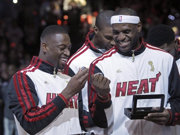 Miami Heat players Wade, and James hold their championship rings from the 2012 season after they received them during a ceremony in Miami