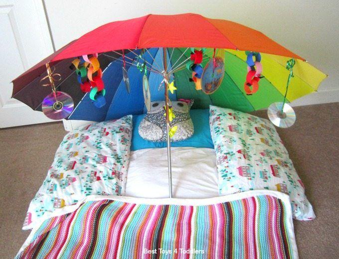Hier kan je het kindje onder de paraplu leggen en kan het kind spelen met het materiaal dat aan de paraplu hangt.