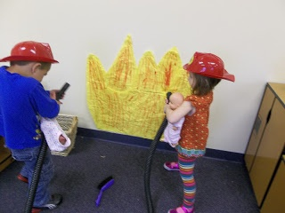 The children had fireman helmets and a hose to help put out the flames in our classroom.