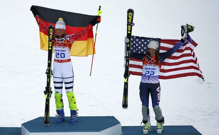 Winner Germany's Maria Hoefl-Riesch (L) and third-placed Julia Mancuso of the U.S. hold up their flags on the podium during the victory cere...
